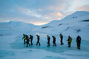 UNIS professor Doug Benn (left) and his students cross a frozen meltwater pool on Tellbreen, Svalbard.