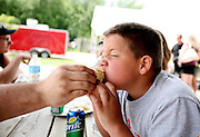Mateus Saltzman, 8, gets a bite of brat with kraut from his dad, Trapper Saltzman, at Sauerkraut Days in Henderson, MN, June 23, 2012.  The two traveled from Viborg, South Dakota, to compete in the arm wrestling competition held at the festival.