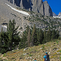 A mother and son hike up Big Pine Canyon in California's eastern Sierra Nevada.   !3,000-foot Temple Crag towers above them.