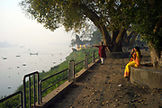A man and a woman do yogic exercises at dawn on the banks of Hooghley River, Chandannagar, India