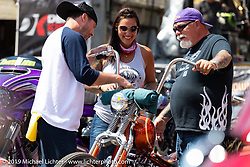 Jody and Dave Perewitz talking with custom bike builder Joe Marshall at their Perewitz Paint annual bike show at the Iron Horse Saloon during the Sturgis Black Hills Motorcycle Rally. SD, USA. Wednesday, August 7, 2019. Photography ©2019 Michael Lichter.