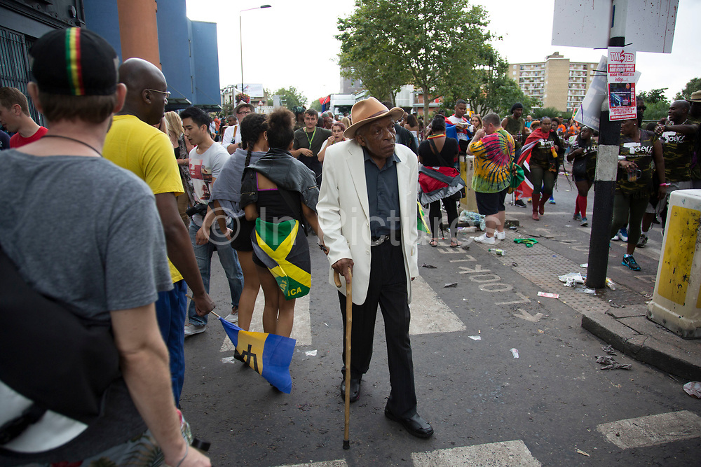 Elderly member of the Caribbean community looking sharp on Sunday 28th August 2016 at the 50th Notting Hill Carnival in West London. A celebration of West Indian / Caribbean culture and Europes largest street party, festival and parade. Revellers come in their hundreds of thousands to have fun, dance, drink and let go in the brilliant atmosphere. It is led by members of the West Indian / Caribbean community, particularly the Trinidadian and Tobagonian British population, many of whom have lived in the area since the 1950s. The carnival has attracted up to 2 million people in the past and centres around a parade of floats, dancers and sound systems.