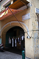 Clothing hangs to dry in the archway of an old colonial style storefront in Macau.