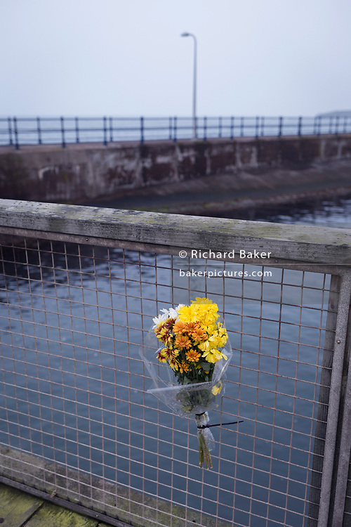 A single sad bouquet of dying flowers are attached to the fence of a Northumbrian North Sea town harbour, on 25th September 2017, in Amble, Northumberland, England.