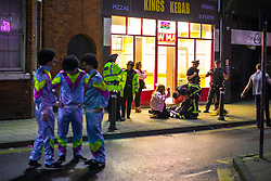© Licensed to London News Pictures . 27/12/2017. Wigan, UK. Police officers ensure a man, dressed up as a fireman, is well, after a fall . Revellers in Wigan enjoy Boxing Day drinks and clubbing in Wigan Wallgate . In recent years a tradition has been established in which people go out wearing fancy-dress costumes on Boxing Day night . Photo credit: Joel Goodman/LNP