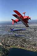 Flying inverted in the foreground, aerobatic Pilot Sean D. Tucker flies his Oracle Challenger III with Blue Angel pilots Lt. Dave Tickle in #6 and Lt. C. J. Simonsen in #5, center, over the Seattle skyline. (Greg Gilbert  / The Seattle Times, 2015)