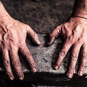 Die rußgeschwärzten Hände eines Messerschmieds am Amboss, Garmisch-Partenkirchen, Bayern, Deutschland.