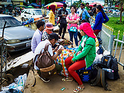 05 JULY 2017 - POIPET, CAMBODIA: Cambodian migrant workers going to Thailand snack on Cambodian treats before crossing the Thai border. Cambodian migrant workers in Poipet headed for Thailand take a tuk-tuk (three wheeled taxi) to the Thai-Cambodian border. The Thai government proposed new rules for foreign workers recently. The new rules include fines of between 400,000 and 800,00 Thai Baht ($12,000 - $24,000 US) and jail sentences of up to five years for illegal workers and people who hire illegal workers. Hundreds of companies fired their Cambodian and Burmese workers and tens of thousands of workers left Thailand to return to their countries of origin. Employers and human rights activists complained about the severity of the punishment and sudden implementation of the rules. On Tuesday, 4 July, the Thai government suspended the new rules for 180 days and the Cambodian and Myanmar governments urged their citizens to stay in Thailand, but the exodus of workers continued through Wednesday.     PHOTO BY JACK KURTZ
