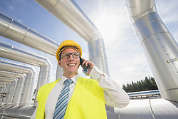 Young engineer talking on mobile phone at geothermal power station, Bavaria, Germany