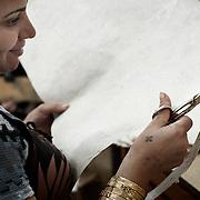 """El Proyecto de Reciclado de Papel en el taller de la ONG A.P.E., nació de la idea de fomentar la capacidad de autogestión y las mejorar las perspectivas de futuro de las mujeres jovenes en Mokattam , la mujer lleva tatuada la cruz copta en la mano. En medio del barrio de Manshiet Nasr a las afueras de El Cairo esta situado el asentamiento de Mokattam conocido como la """"Ciudad de la Basura"""" , está habitado por los Zabbaleen ,una comunidad de unos 45.000 cristianos coptos que viven desde hace varias décadas de reciclar los desperdicios que genera la capital egipcia: plástico, aluminio, papel y desechos órganicos que transforman en compost . La mayoría forman parte de la Asociación para la Protección del Ambiente (APE) una ONG que actúa en el área, cuyos objetivos son proteger el medio ambiente y aumentar el sustento de las recuperadores de basura de El Cairo. Según la ONU, el trabajo que se realiza en Mokattam como uno de los diez mejores ejemplos del mundo en el mejoramiento medioambiental. El Cairo , Egipto, Junio 2011. ( Foto : Jordi Camí )"""