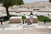 Israel, Negev, Kibbutz Sde Boker, the grave of David (right) and Pola (left) Ben Gurion The Desert in the background. Female tourist placing stone on grave. Model release available July 2008