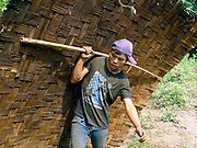 "A Laoseng ethnic minority man carries a bamboo house wall to the new village from the old village of Ban Phoumeuang  which is being temporarily relocated away from the Nam Ou river, during the construction of the Nam Ou Cascade Hydropower Project Dam 6. The Nam Ou river connects small riverside villages and provides the rural population with food for fishing. It is a place where children play and families bathe, where men fish and women wash their clothes. But this river and others like it, that are the lifeline of rural communities and local economies are being blocked, diverted and decimated by dams. The Lao government hopes to transform the country into ""the battery of Southeast Asia"" by exporting the power to Thailand and Vietnam."