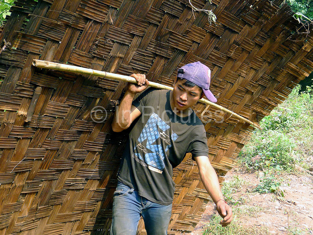 """A Laoseng ethnic minority man carries a bamboo house wall to the new village from the old village of Ban Phoumeuang  which is being temporarily relocated away from the Nam Ou river, during the construction of the Nam Ou Cascade Hydropower Project Dam 6. The Nam Ou river connects small riverside villages and provides the rural population with food for fishing. It is a place where children play and families bathe, where men fish and women wash their clothes. But this river and others like it, that are the lifeline of rural communities and local economies are being blocked, diverted and decimated by dams. The Lao government hopes to transform the country into """"the battery of Southeast Asia"""" by exporting the power to Thailand and Vietnam."""