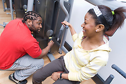 Fitness instructor showing a young woman how to use the chest press machine at her sports leisure centre,