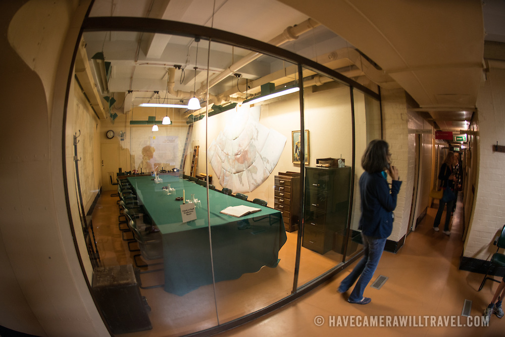 A museum visitor stands in front of the Chiefs of Staff Conference Room at the Churchill War Rooms in London. The museum, one of five branches of the Imerial War Museums, preserves the World War II underground command bunker used by British Prime Minister Winston Churchill. Its cramped quarters were constructed from a converting a storage basement in the Treasury Building in Whitehall, London. Being underground, and under an unusually sturdy building, the Cabinet War Rooms were afforded some protection from the bombs falling above during the Blitz.