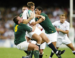 No mobile phone use, Internet sites may only use one image every five minutes during match:  England's Will Greenwood (centre left) is tackled by Corne Krige (left) and Ashwin Willemse of South Africa during their Rugby World Cup match at the Subiaco Stadium, Perth, Australia. England won 25-6.