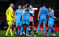 Barnet's David Tutonda (centre) and Brentford's Sergi Canos congratulate each other at the end of the FA Cup fourth round replay match at Griffin Park, London.