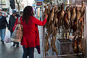 Woman checking the qulaity of pheasants hanging up outside a traditional British butchers shop on Bethnal Green Road, London, UK. Once a White British area, the multicultural mix here is predominantly made up of Bangladeshi and other ethnic groups, which seems almost at odds with the areas diversity.