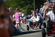 Clyde Boatright with the Calam Temple Shriners gives a go-karting high five to Nikki Timmins and her daughter, Kya, during the Rathdrum Days Parade on Saturday.