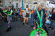 Extinction Rebellion climate change activists drumming and hula hooping as sites around Westminster are blocked on 8th October 2019 in London, England, United Kingdom. Extinction Rebellion is a climate group started in 2018 and has gained a huge following of people committed to peaceful protests. These protests are highlighting that the government is not doing enough to avoid catastrophic climate change and to demand the government take radical action to save the planet.