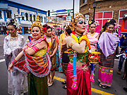 """29 APRIL 2017 - MINNEAPOLIS, MINNESOTA: People in traditional Thai costumes prepare for the parade at Songkran Uptown. Several thousand people attended Songkran Uptown on Hennepin Ave in Minneapolis for the city's first celebration of Songkran, the traditional Thai New Year. Events included a Thai parade, a performance of the Ramakien (the Thai version of the Indian Ramayana), a """"Ladyboy"""" (drag queen) show, and Thai street food.     PHOTO BY JACK KURTZ"""