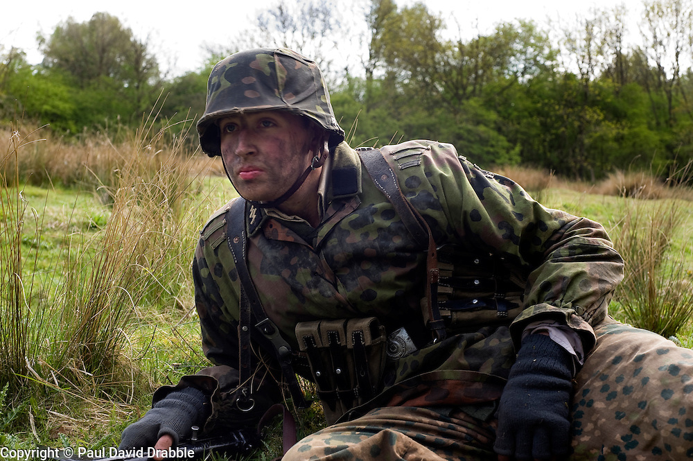 A reenactor portraying a member of the Waffwn SS takes part in a Private Training Weekend in Yorkshire. The SS runes can been seen on the right collar. He is dressed in pea dot and Oak leaf camouflage wearing the classic German Steel Helmet (stahlhelm) which also has a camouflage cover and is Armed with a sub machine gun  Images © Paul David Drabble.