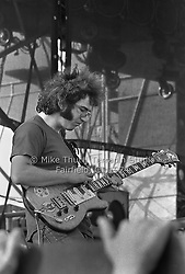 Jerry Garcia getting intense, playing Guitar, watching his handywork. The Grateful Dead at Dillon Stadium in Hartford CT on 31 July 1974. Close in sidelong shot with a fan grasping at the stage. Photo by Michael Thut, Fairfield CT.
