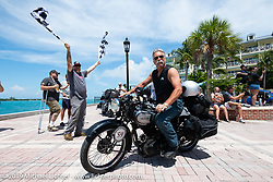 Mark Zenor riding his 1946 Norton Model 18 over the finish line at the end of the Cross Country Chase motorcycle endurance run from Sault Sainte Marie, MI to Key West, FL. (for vintage bikes from 1930-1948). The Grand Finish in Key West's Mallory Square after the 110 mile Stage-10 ride from Miami to Key West, FL and after covering 2,368 miles of the Cross Country Chase. Sunday, September 15, 2019. Photography ©2019 Michael Lichter.