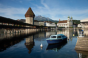 A docked boat in front of the Chapel Bridge and Mount Pilatus in the distance, Lucerne, Switzerland.