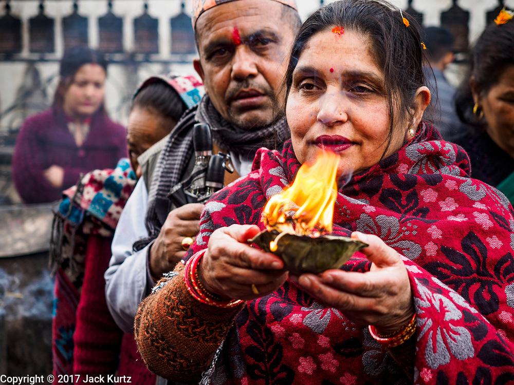 11 MARCH 2017 - KATHMANDU, NEPAL:  Nepali Hindus pray at a Hindu shrine at Swayambhu Stupa. The second most important Buddhist stupa in Kathmandu, Swayambhu Stupa is also a historic landmark and has panoramic views of Kathmandu. It is sacred to both Buddhists and Hindus. The stupa is being rebuilt because it was badly damaged in the 2015 earthquake.   PHOTO BY JACK KURTZ