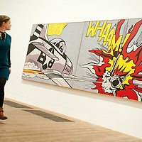 London, UK - 18 February 2013: a Tate employee walks in front of 'Whaam!' during the  'Lichtenstein: A Retrospective' exhibition that opens at Tate Modern in London on the 21st of February. The exhibition is the first major Lichtenstein retrospective for twenty years, bringing together over 125 of the artist's most definitive paintings and sculptures. Built on new research and scholarship, the exhibition reassesses Lichtenstein's work and his enduring legacy.