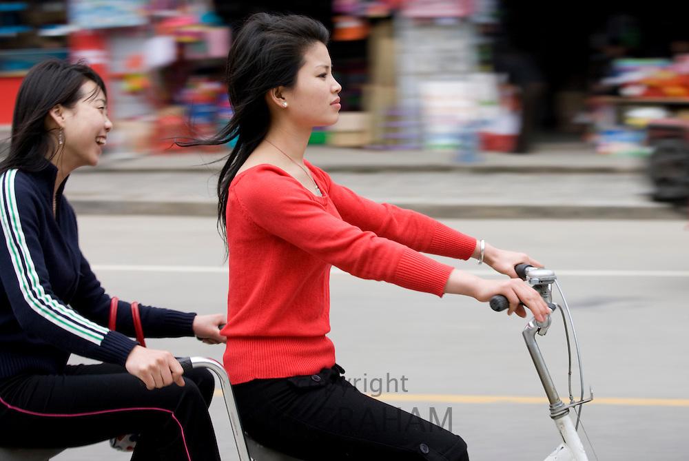 Girls on a tandem bike in Yangshuo street, China