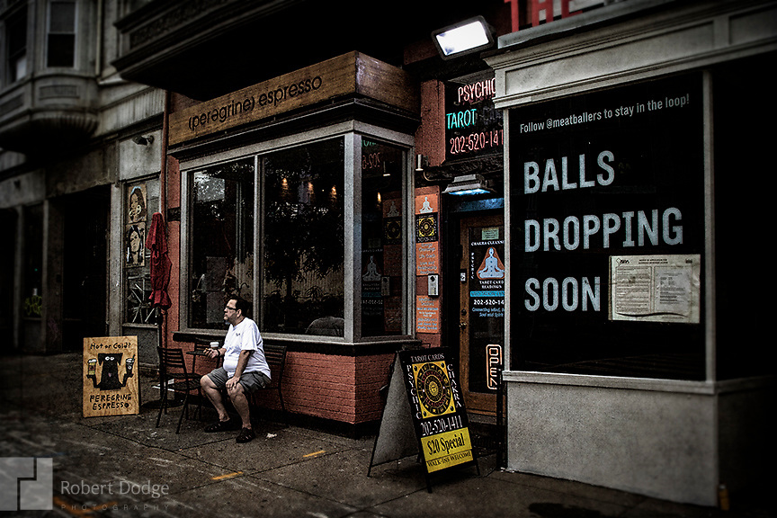 """A man passes the day sitting on a bench in front of a coffee shop. Next door is a sign announcing the opening of a Meatball Shop restaurant. You wonder who's balls will be dropping soon. A dapper dandy makes his way up the street from grocery shopping -- perhaps eager to taste the goodies he just purchased. This image is from Robert Dodge """"Project: 14th and U Streets,"""" a look at the center of town in Washington, D.C. For info on publication or fine-art-, limited-edition prints, contact: Robert@RobertDodge.com."""