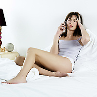 young hangover sad woman on the phone  in her bedroom