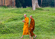 Two Buddhist monks walking and talking at Angkor Thom Temple, Angkor Wat Archeological Park, Siem Reap, Cambodia.