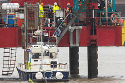 © Licensed to London News Pictures. 25/07/2020. London, UK. Specialist police remove an Extinction Rebellion activists that locked on to a drilling rig in the Thames close to the 02 Arena in Greenwich this morning . The rig is involved with preparatory drilling for the Silvertown Tunnel which is planned to connect the Greenwich Peninsula with west Silvertown. Extinction Rebellion oppose the building of the tunnel due to the increase in air pollution it may cause. Photo credit: George Cracknell Wright/LNP