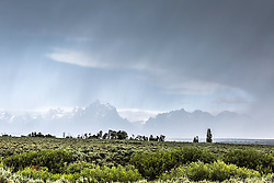 """Jackson Hole thunderstorm, a promise of sun beyond.  The hole in the storm reveals the jagged peaks of the Grand Tetons in Grand Teton National Park<br /> <br /> For production prints or stock photos click the Purchase Print/License Photo Button in upper Right; for Fine Art """"Custom Prints"""" contact Daryl - 208-709-3250 or dh@greater-yellowstone.com"""