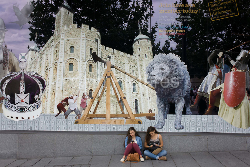 Young tourist women sit beneath the large UK tourism window featuring famous landmarks, at the Tower of London. London tourism attractions at the Tower are seen on this large illustration opposite the famous building. The girls enjoy a quiet moment among the throng of visitors to the UK capital. Her Majesty's Royal Palace and Fortress, known as the Tower of London, is a historic castle located on the north bank of the River Thames in central London. It was founded towards the end of 1066 as part of the Norman Conquest of England. The White Tower, which gives the entire castle its name, was built by William the Conqueror in 1078, and was a resented symbol of oppression, inflicted upon London by the new ruling elite.