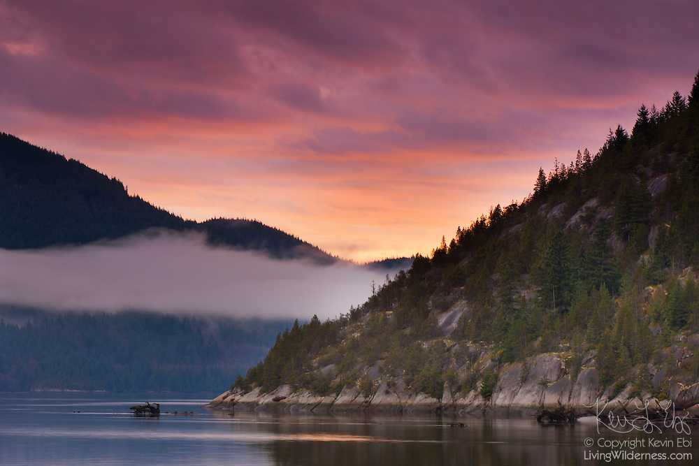 A layer of low clouds and fog blows in at sunset over Howe Sound near Squamish, British Columbia, Canada. This view was captured from the spit located in the Squamish River Estuary.