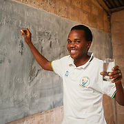 A professor at a high school in Kisaro Sector, Rulindo District, Rwanda, hold a glass of safe drinking water.