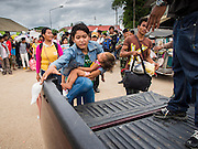 16 JUNE 2014 - ARANYAPRATHET, THAILAND: A Cambodian migrant woman and her child climb into a Thai police vehicle. More than 150,000 Cambodian migrant workers and their families have left Thailand since June 12. The exodus started when rumors circulated in the Cambodian migrant community that the Thai junta was going to crack down on undocumented workers. About 40,000 Cambodians were expected to return to Cambodia today. The mass exodus has stressed resources on both sides of the Thai/Cambodian border. The Cambodian town of Poipet has been over run with returning migrants. On the Thai side, in Aranyaprathet, the bus and train station has been flooded with Cambodians taking all of their possessions back to Cambodia. PHOTO BY JACK KURTZ