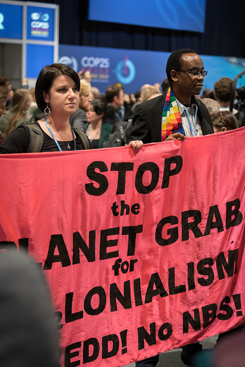"""11 December 2019, Madrid, Spain: """"Stop the planet grab"""" reads a banner, as hundreds of civil society and other actors hold an unauthorized protest outside the plenary hall of COP25 in Madrid, to draw attention to the failures of the climate talks and to call on rich countries to step up and pay up for real solutions, and to highlight the threat of loopholes, false solutions like carbon markets, and the need for those who caused the climate crisis to pay up for loss and damage while respecting human rights."""