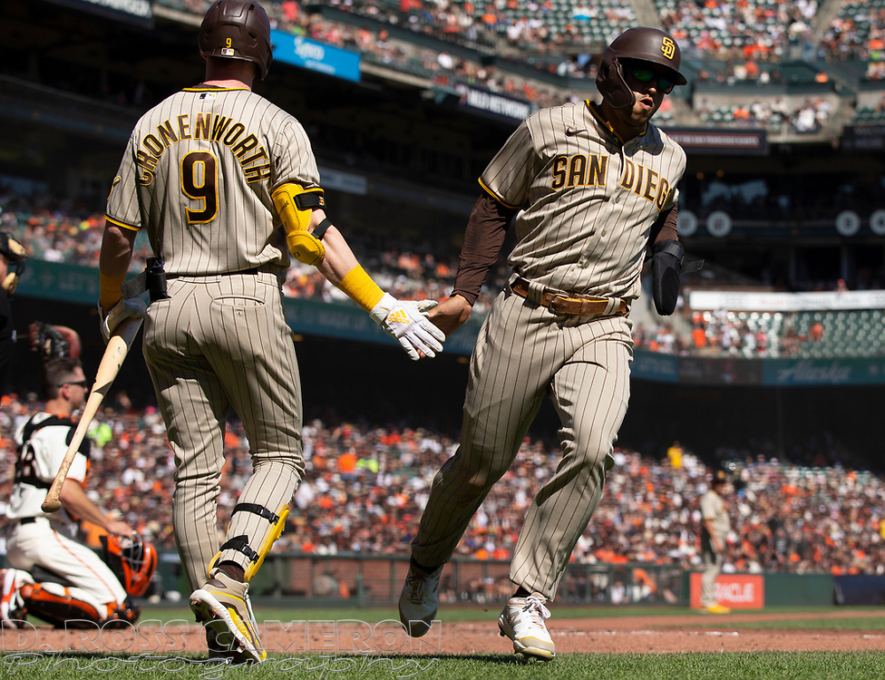 Oct 3, 2021; San Francisco, California, USA; San Diego Padres center fielder Trent Grisham (2) is greeted by teammate Jake Cronenworth as he scores on a sacrifice fly by Manny Machado against the San Francisco Giants during the fourth inning at Oracle Park. Mandatory Credit: D. Ross Cameron-USA TODAY Sports