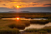 The sun sets over the Parker River National Wildlife Refuge on Plum Island in northeastern Massachusetts. The refuge was established in 1942 to provide habitat for migratory birds. The habitat includes stretches of beach, dunes and saltwater and freshwater marshes. Here the setting sun is reflected on the water of one of the marshes.