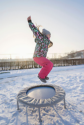 Girl jumping on trampoline on snow field