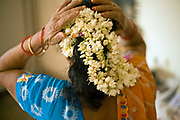 An elderly woman arranges flowers in her hair in her bedroom, Janakpuri, New Delhi, India