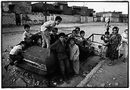 ERBIL, KURDISTAN, IRAQ, 09.09.96. Children play in a car wreck in the outskirts of Erbil. Due to the UN embargo against Iraq and an Iraqi blockade against Kurdistan, the economy is a disaster ©Photo by Frits Meyst/NewsImages
