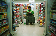 An employee knits a sweater while keeping a watch on a 24hr convenience store in Shanghai, China in 28 December, 2008.  The number of convenient stores such as Lawson and Seven Eleven has exploded in major Chinese cities such as Shanghai and Shenzhen, offering everything from snacks to monthly utility bill payment..
