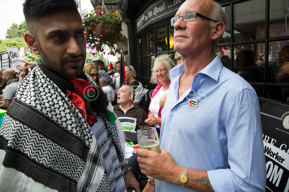 London, UK. Saturday 19th July 2014. Pro-Palestinian protesters in their tens of thousands march through central London to the Israeli Embassy in protest against the military offensive in Gaza by Israel. British protester has a pint outside a pub as demonstrators pass.