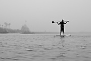 A Man and His Stand Up Paddle in the Calm Ocean Water of Newport Beach Harbor